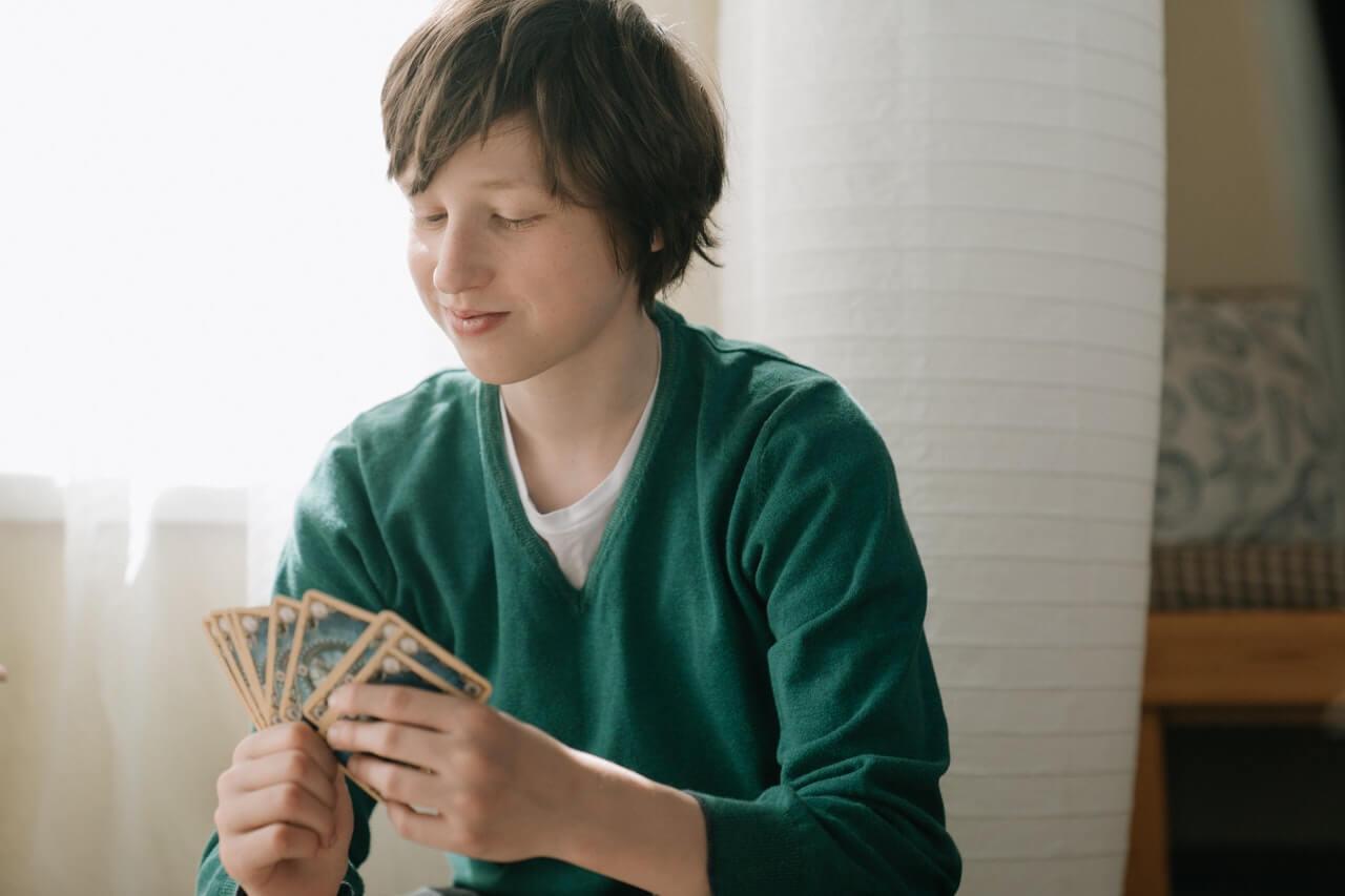 Niño jugando con sus amigos a un juego de cartas.