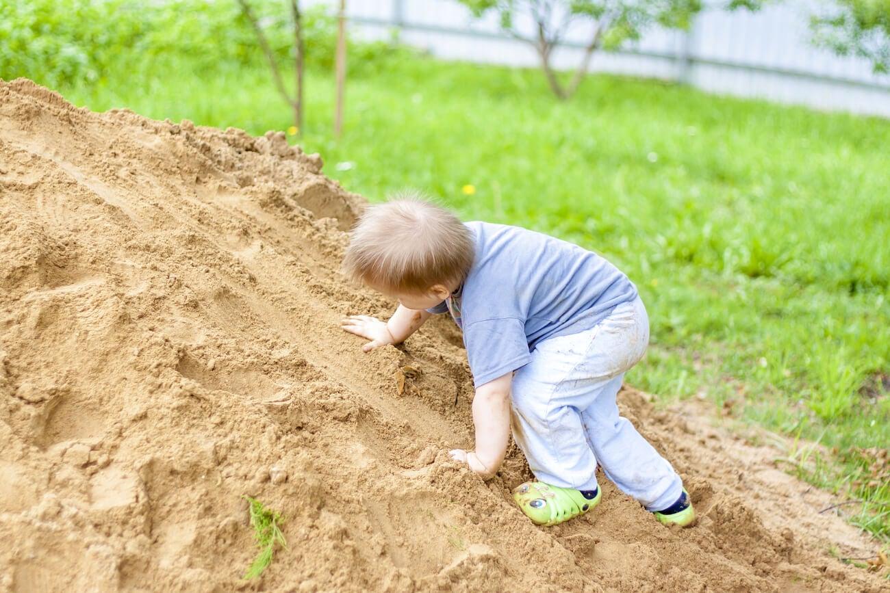 Niño subiendo un montículo de tierra para aprender a asumir riesgos.