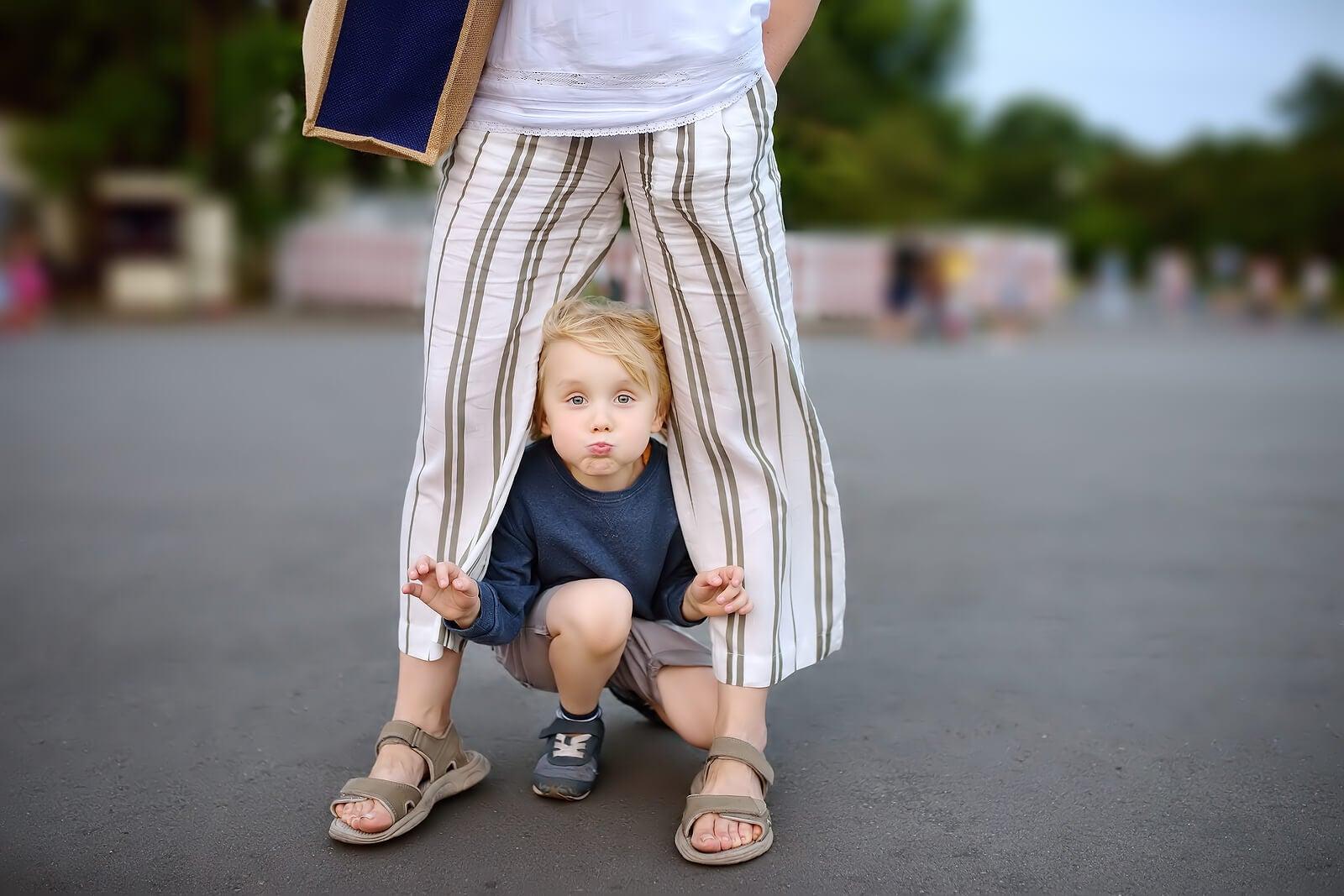 Niño jugando entre las piernas de su madre aplicando la obediencia según Montessori.