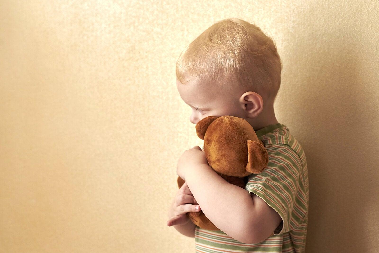 Niño abrazando un peluche porque tiene miedo a la muerte.