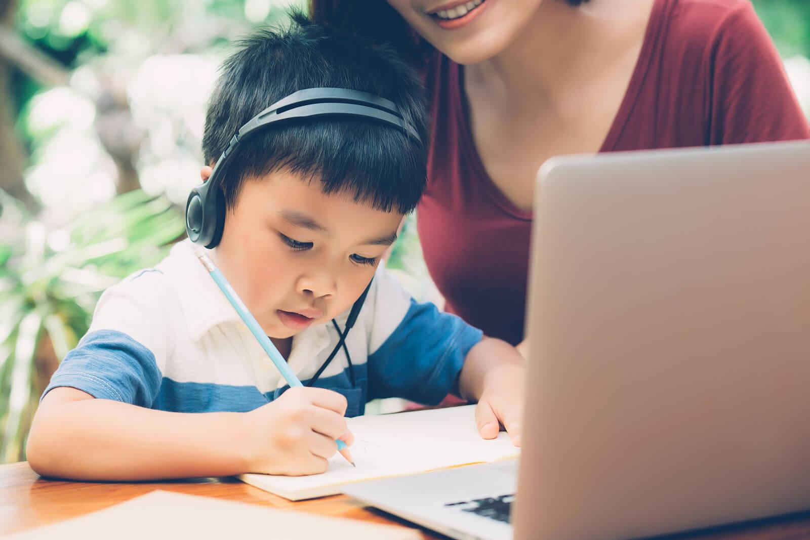 Niño con su madre participando en un taller de escritura creativa online.