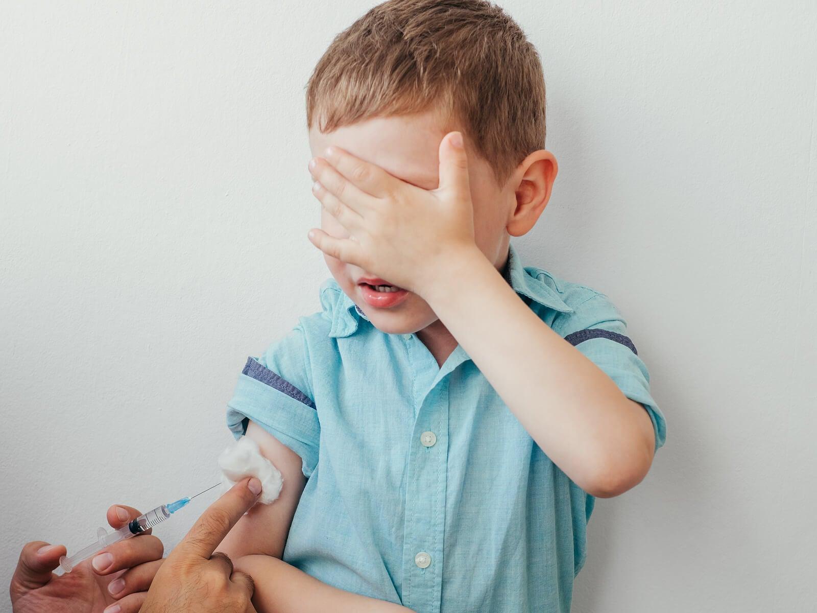 Niño en el pediatra tapándose la cara porque tiene miedo mientras le vacunan.