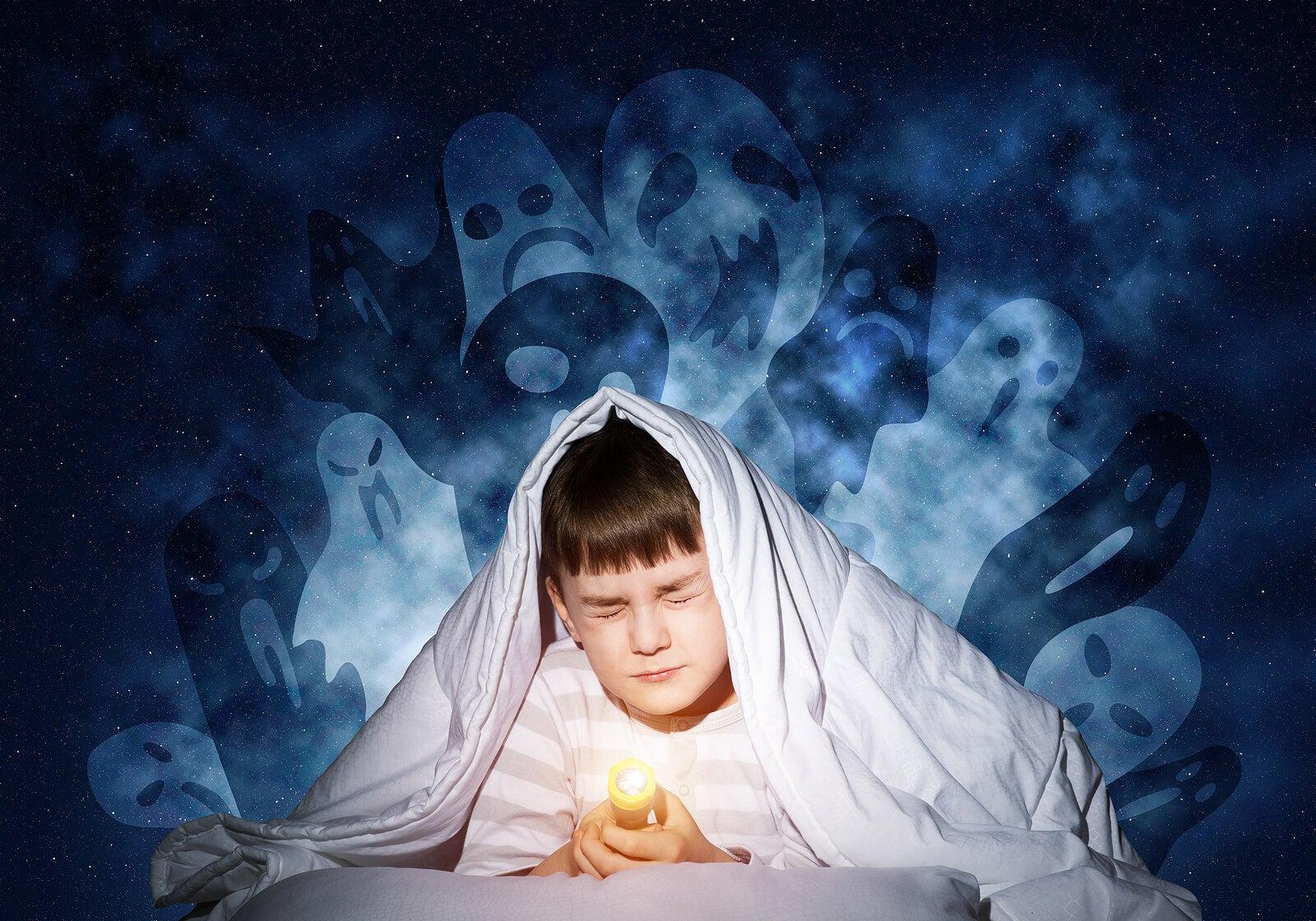 Niño con miedo a los fantasmas se tapa con la sábana en la cama.