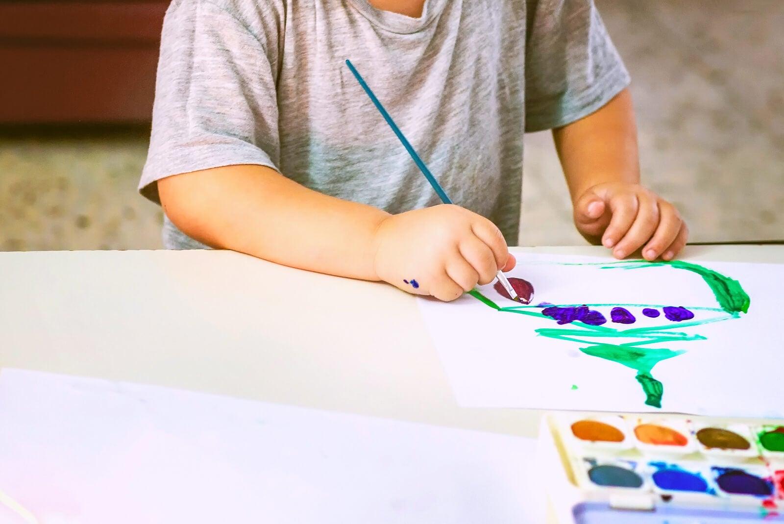 Niño haciendo pintando para poder analizar después sus dibujos.