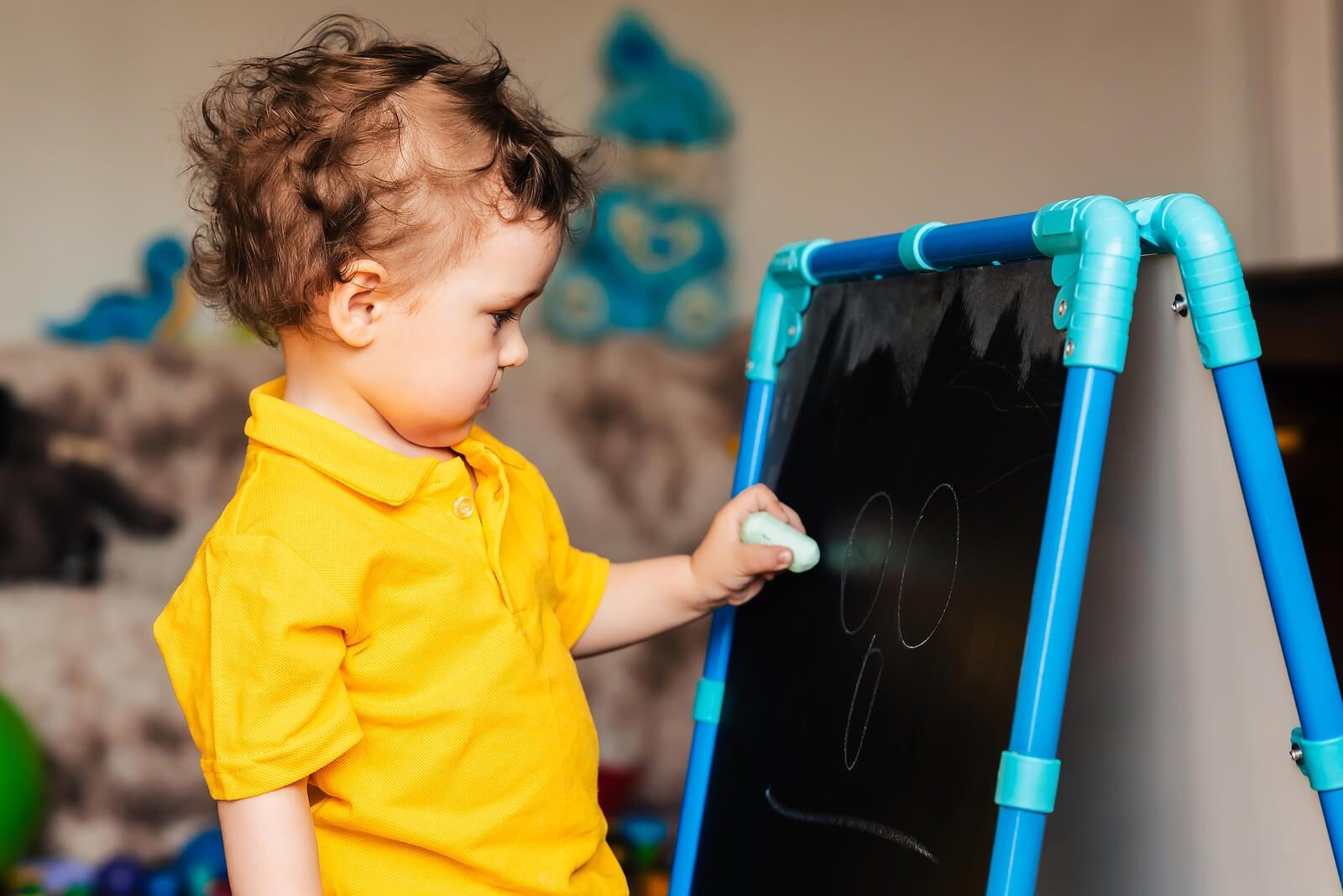 Niño escribiendo en una pizarra para desarrollar el aprendizaje.