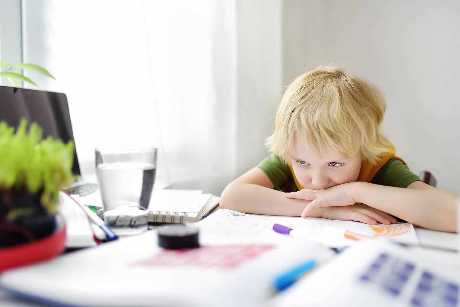 Niño quejándose porque no quiere hacer los deberes.