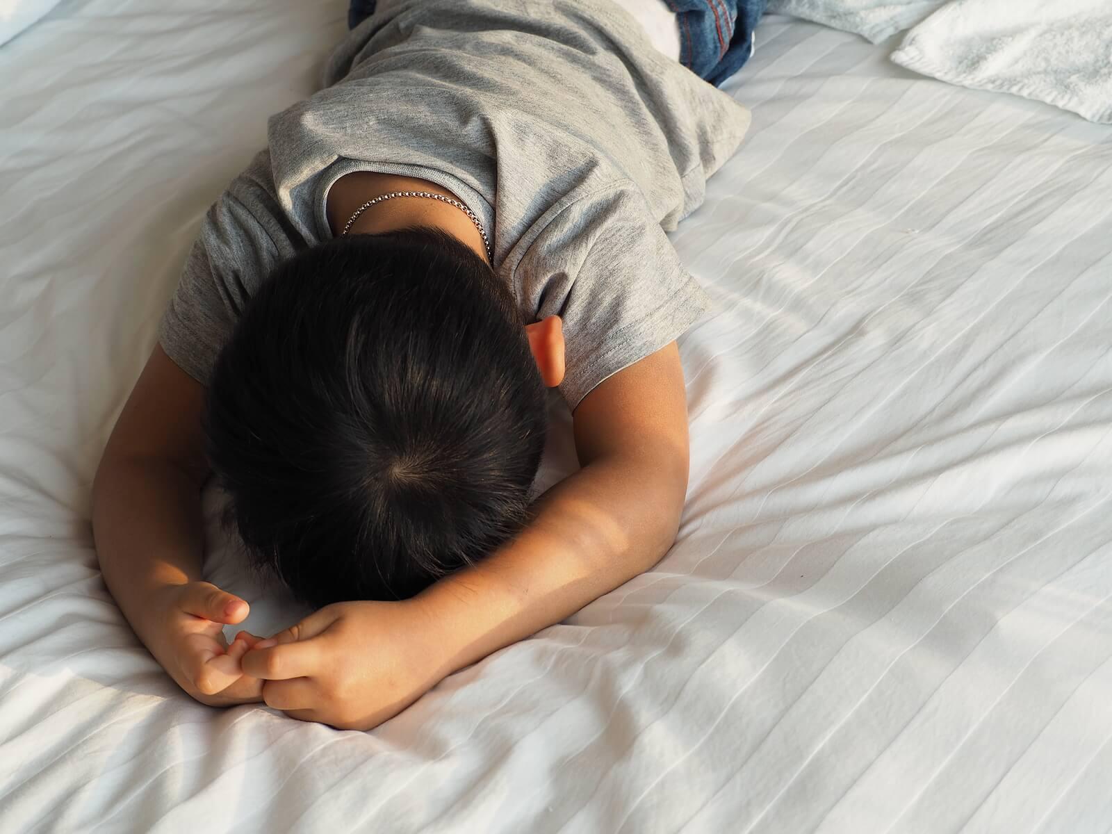 Niño con problemas de autorregulación tumbado en la cama mientras sufre una rabieta.