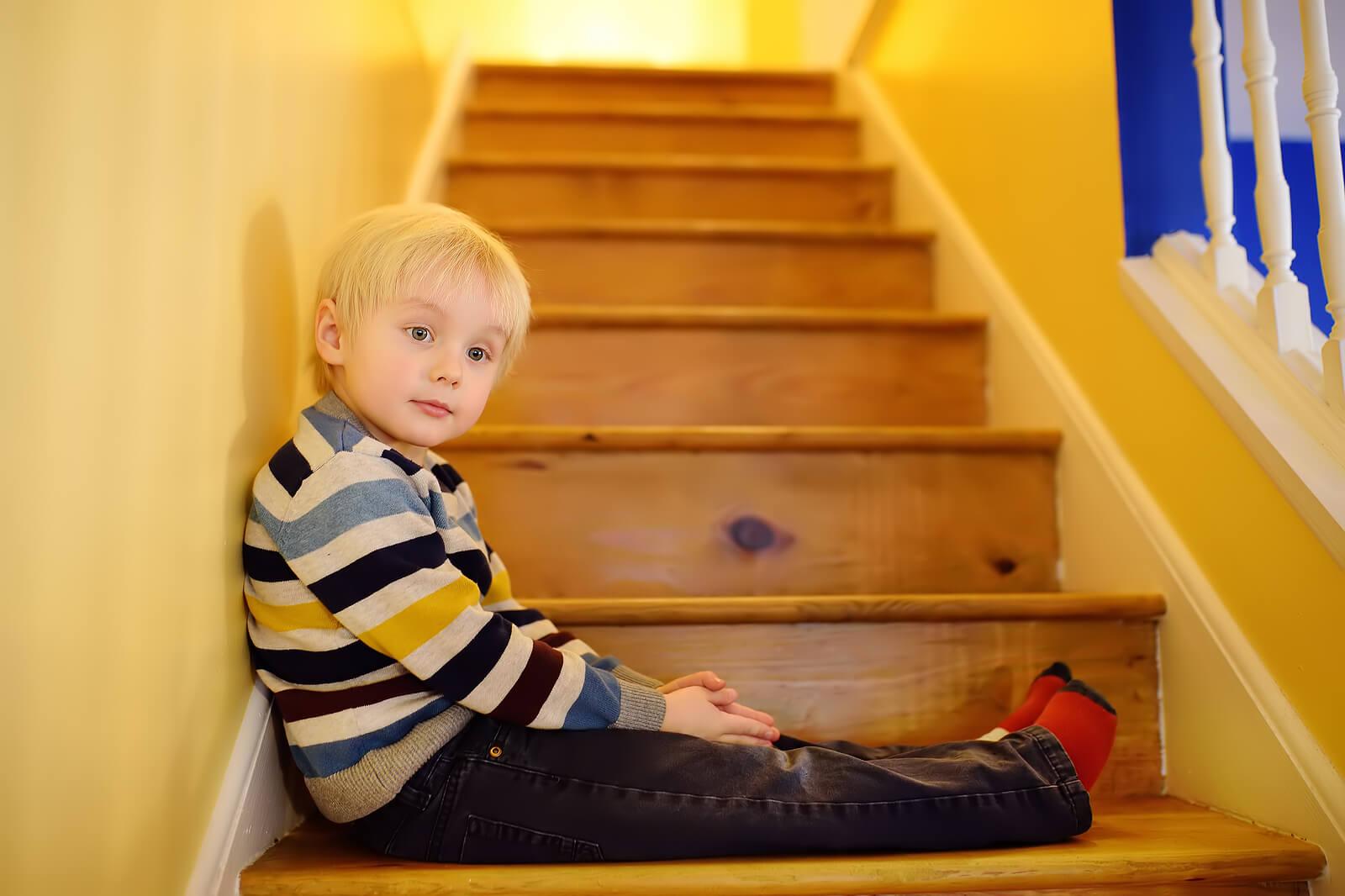 Niño obediente sentado en las escaleras de casa.