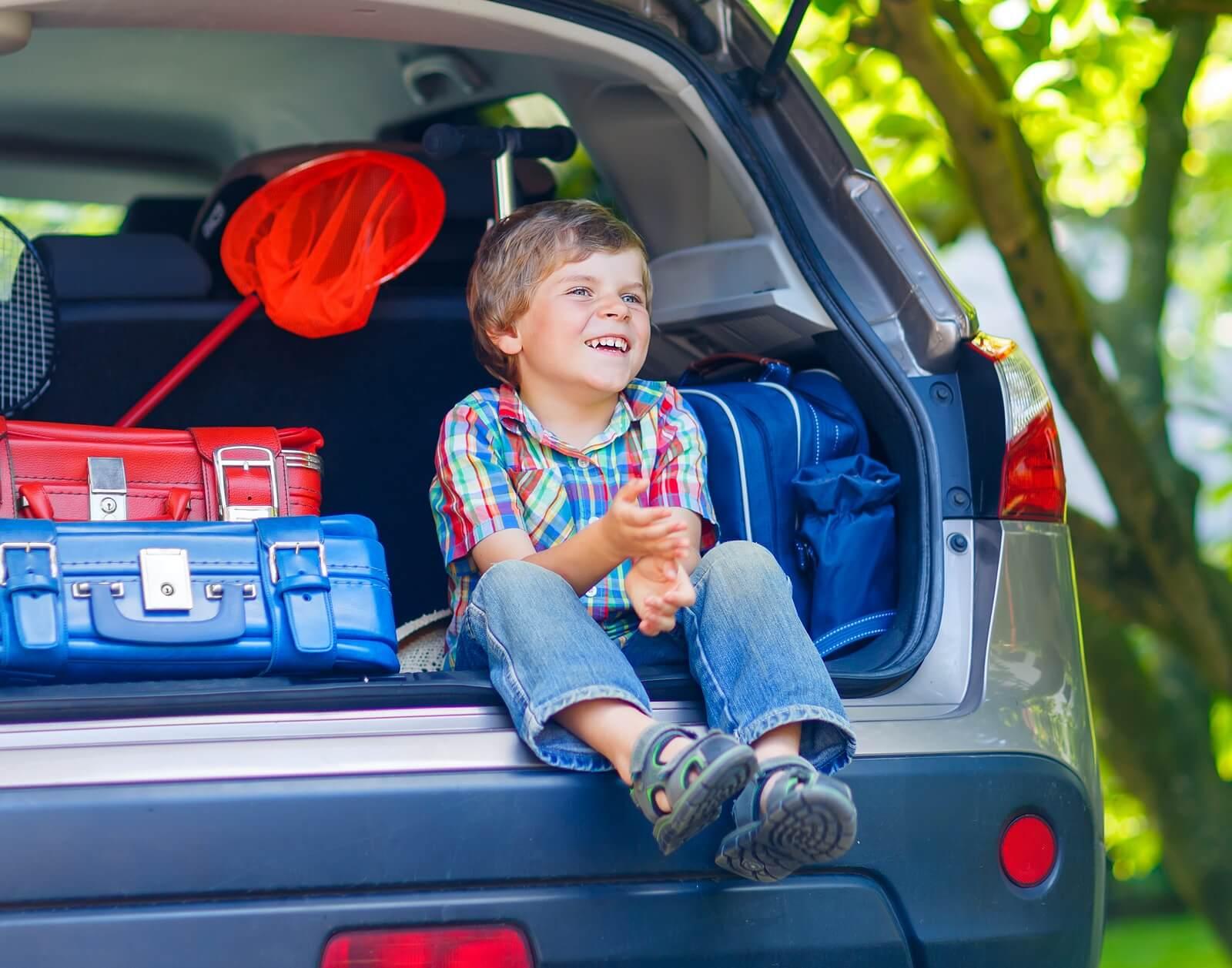 Niño sentado en el maletero del coche antes de hacer un viaje largo con sus padres.