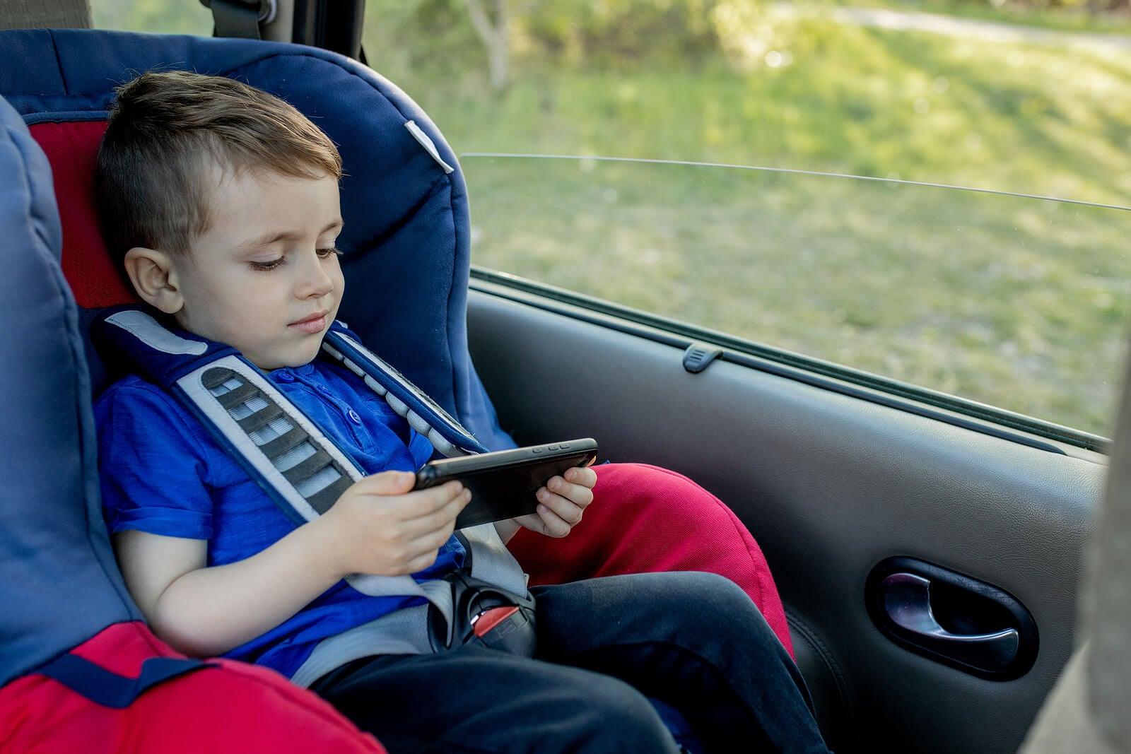 Niño viendo una película en la tablet, una de las actividades para realizar durante viajes largos en coche.