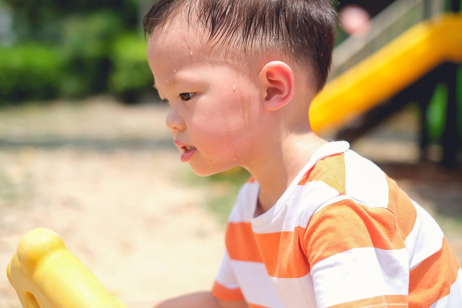 Niño sudando mucho debido a que está jugando al sol.