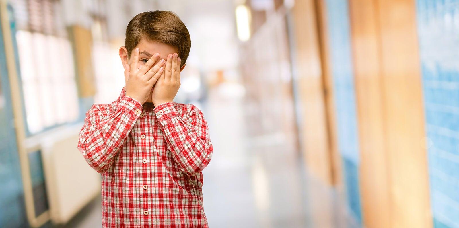 Niño tapándose la cara porque sufre vergüenza tóxica.