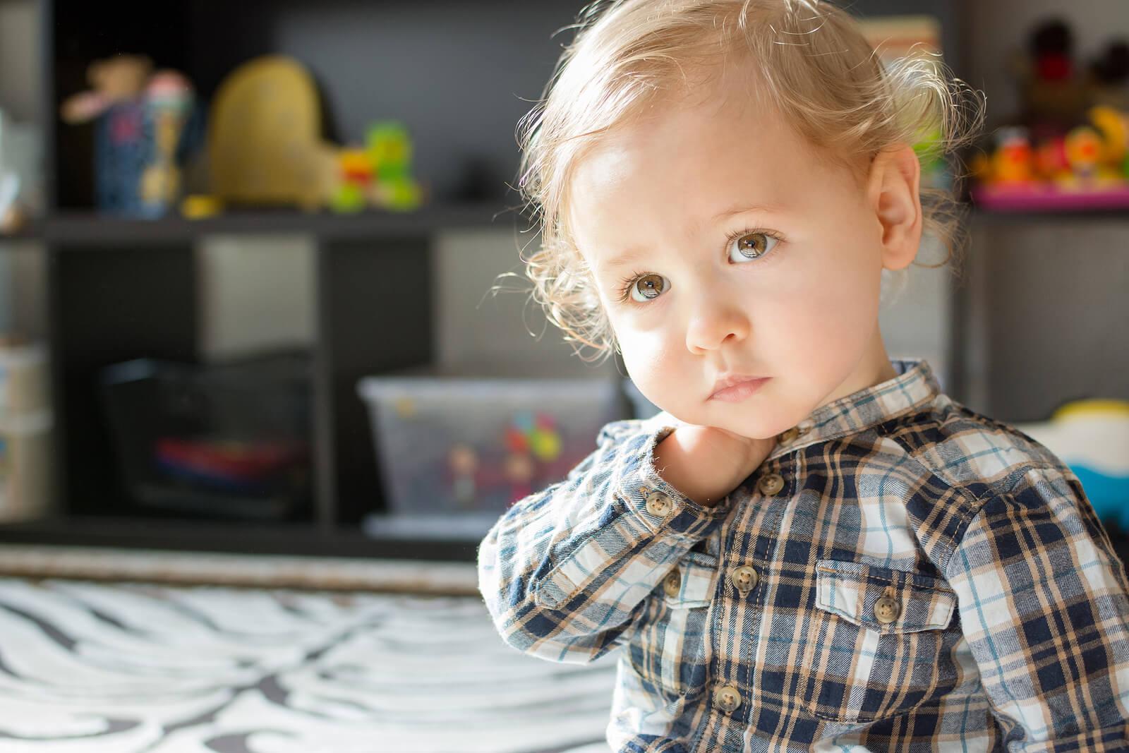Niño pensativo y triste en su habitación.