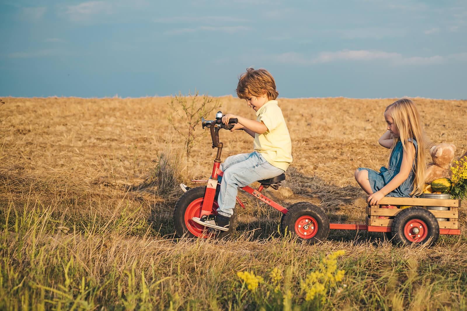 Amigos jugando por el campo con un triciclo a modo de tractor con remolque.