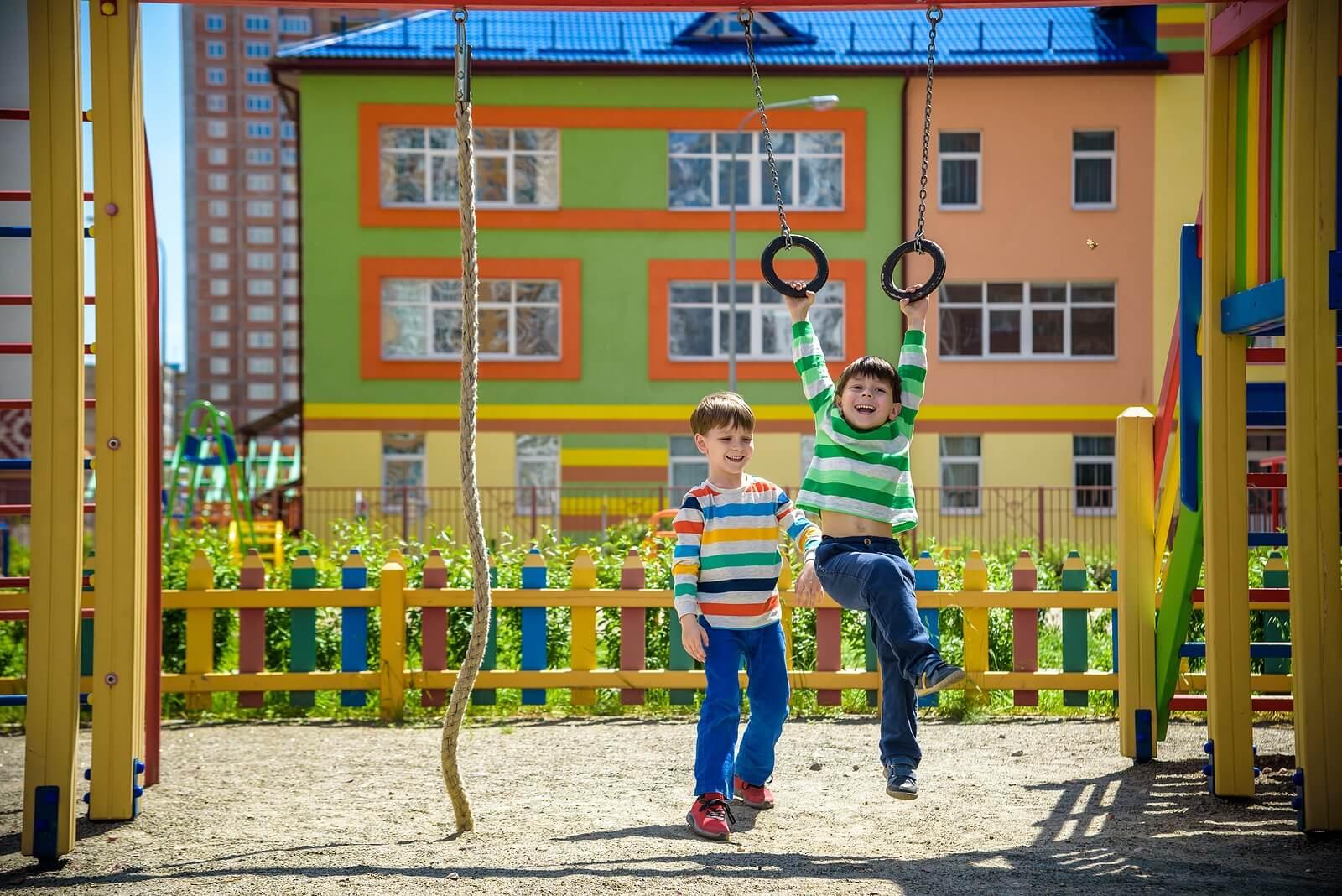 Niños jugando en los columpios cultivando el valor de la amistad.