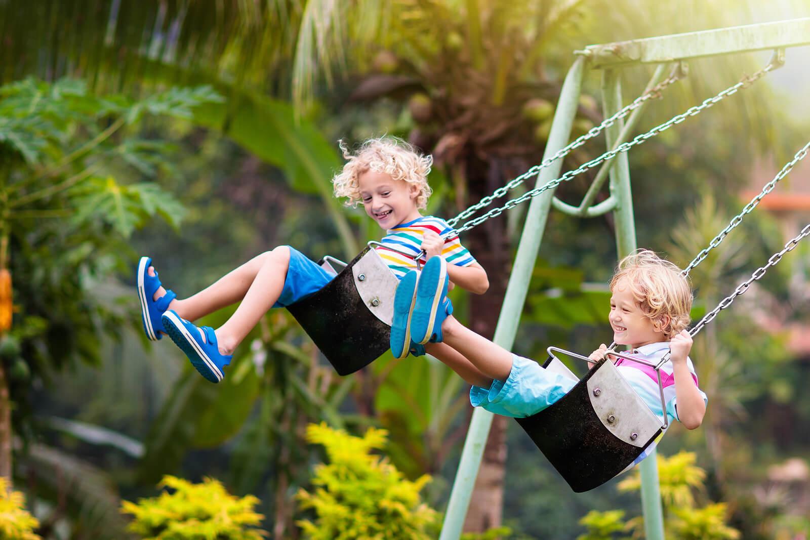 Niño jugando en los columpios del parque infantil.