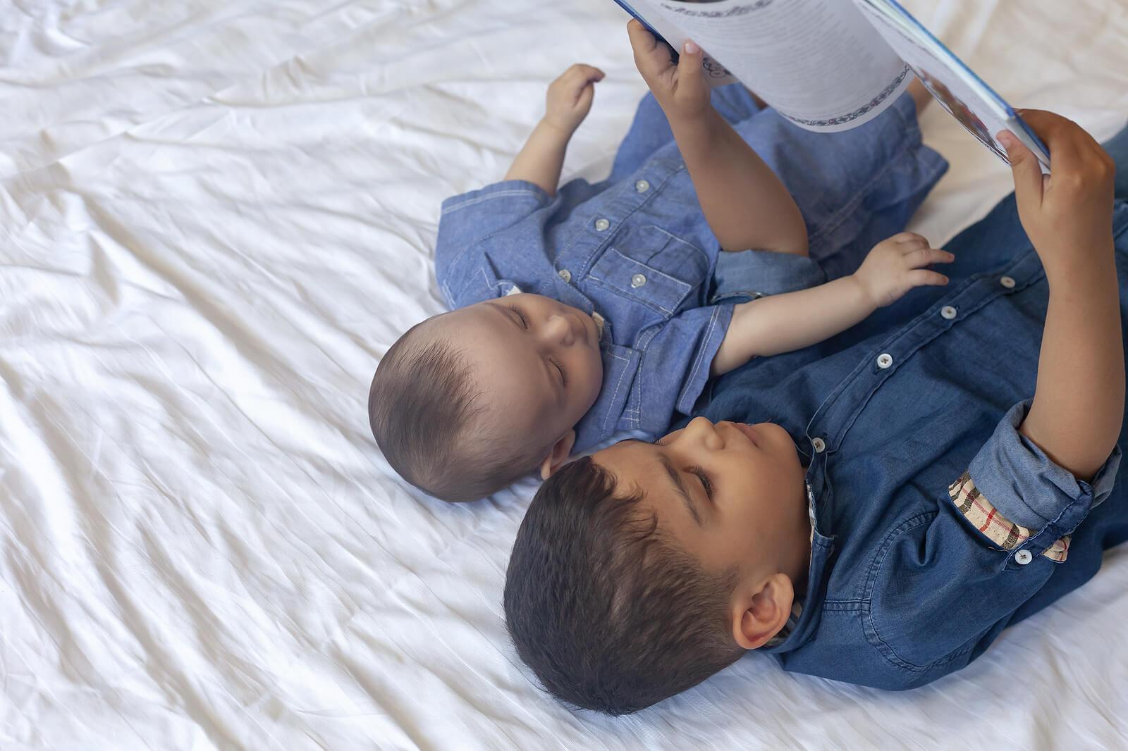 Hermanos leyendo cuentos para combatir la sobrecarga del hermano mayor.