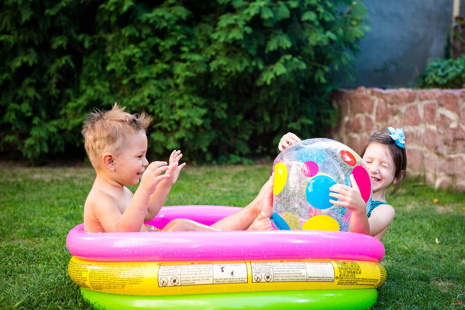 Niño jugando en una piscina hinchable en verano.