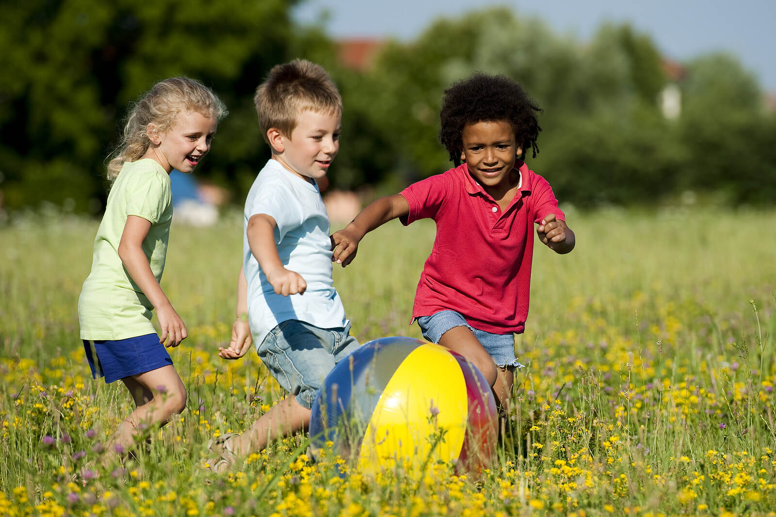 Niños jugando con la pelota al aire libre en verano.