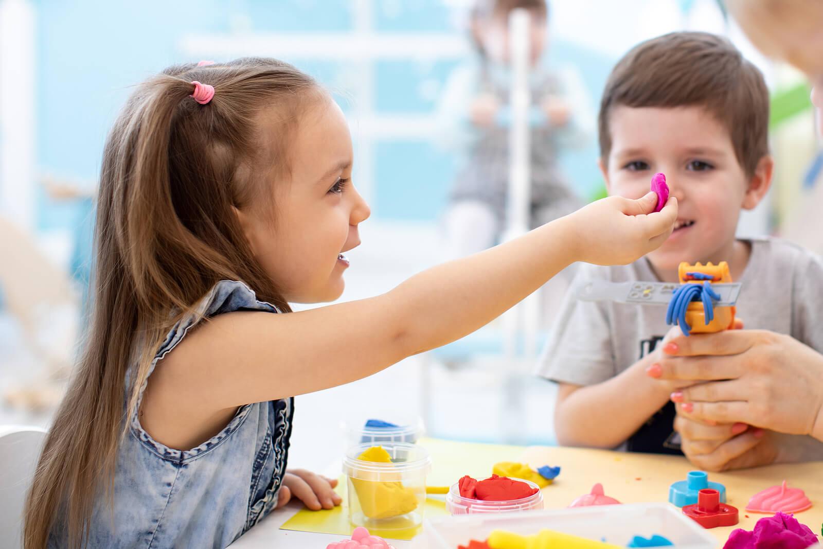 Niño jugando con plastilina haciendo actividades y manualidades sensoriales para niños agitados.