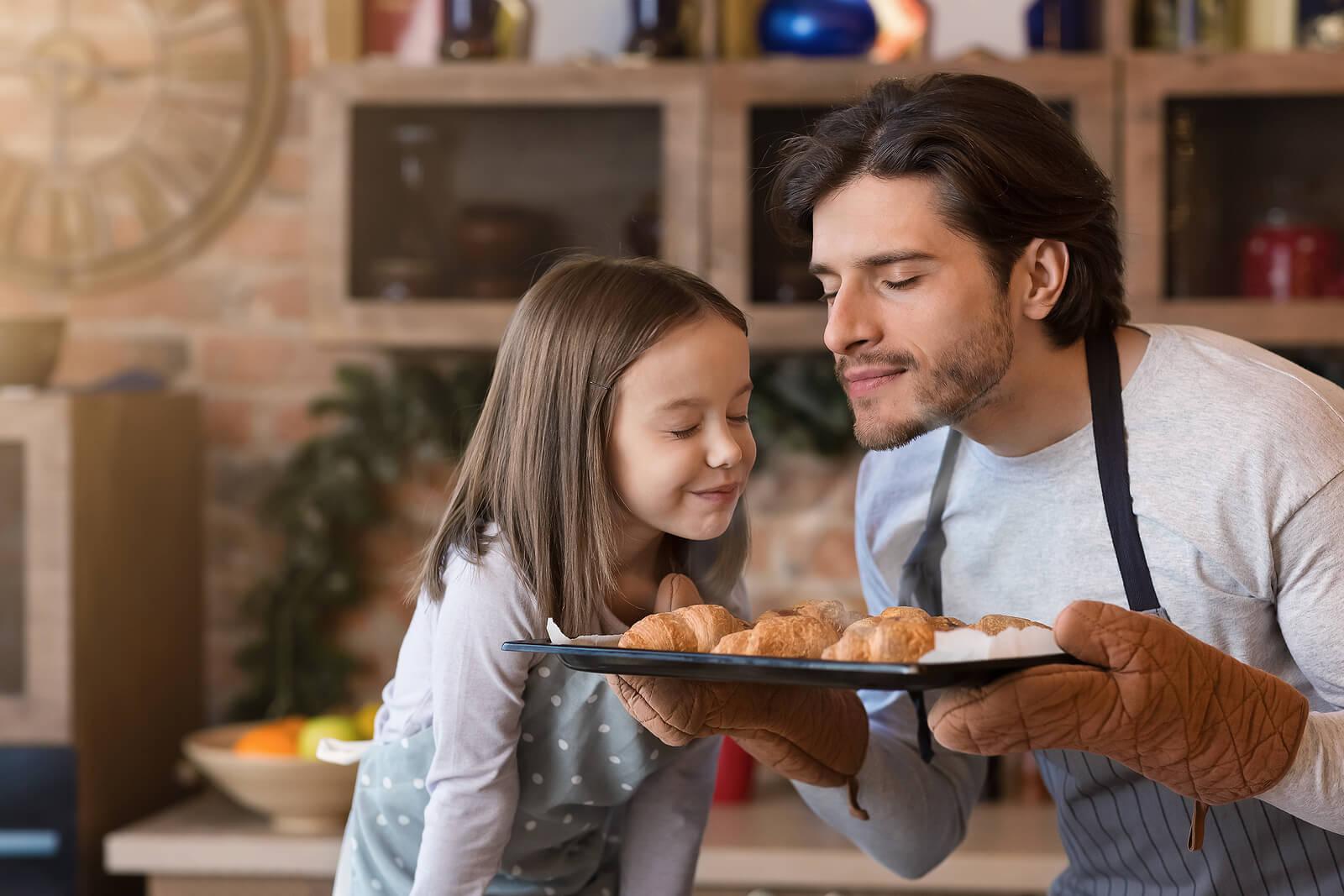 Padre e hija haciendo cruasanes al horno para llenar de olor su recuerdo.