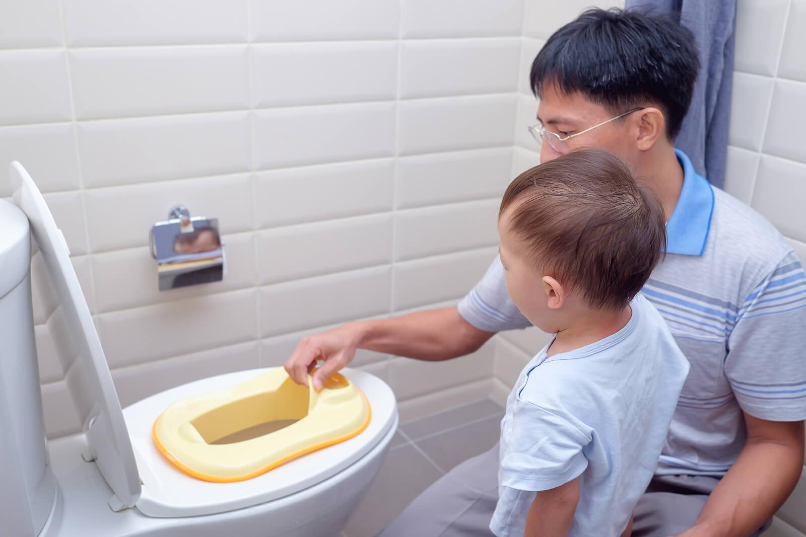 Padre enseñando a su hijo a usar el baño, porque un padre no es una niñera.