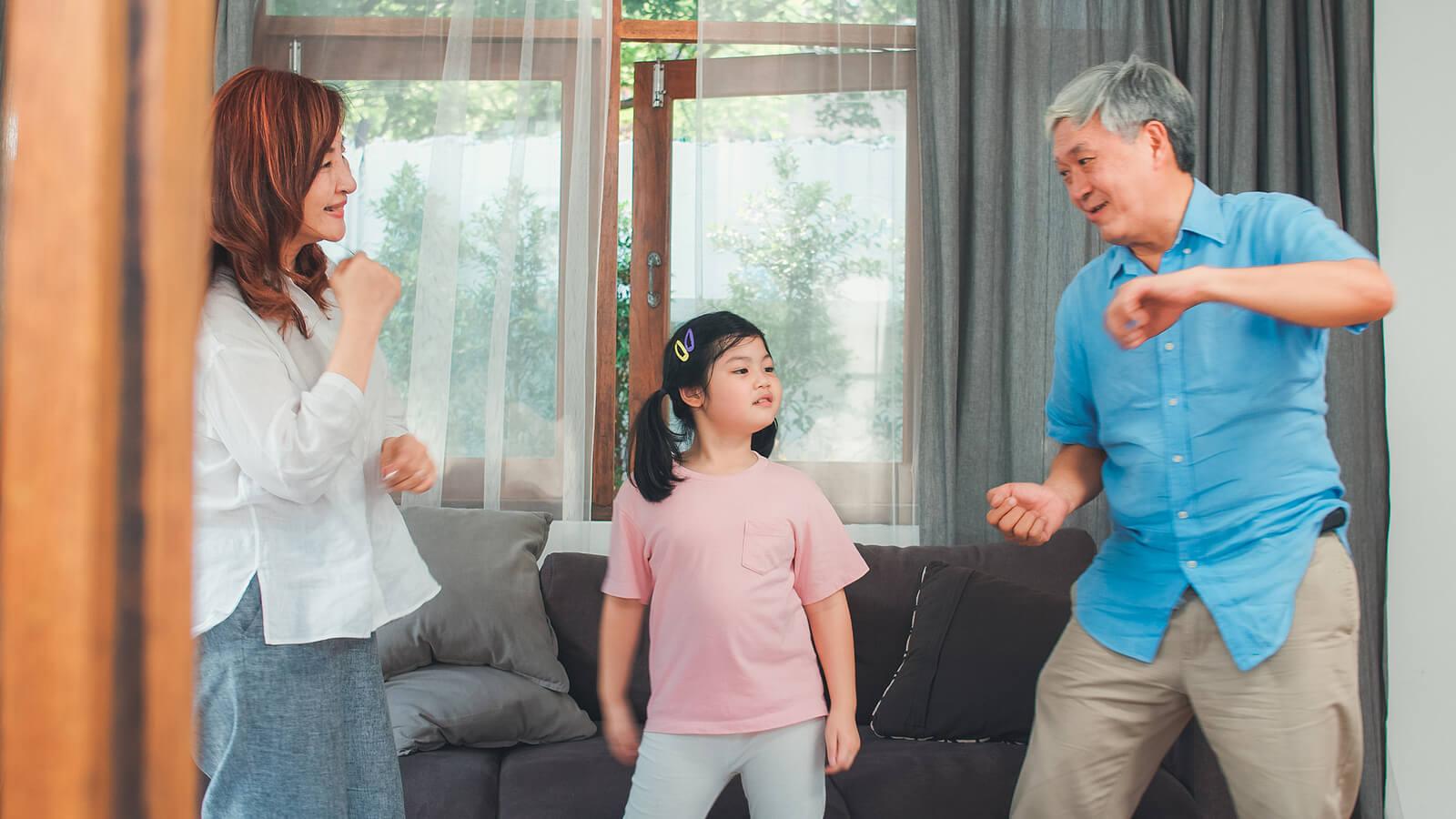 Padres bailando con su hija en el salón de casa.