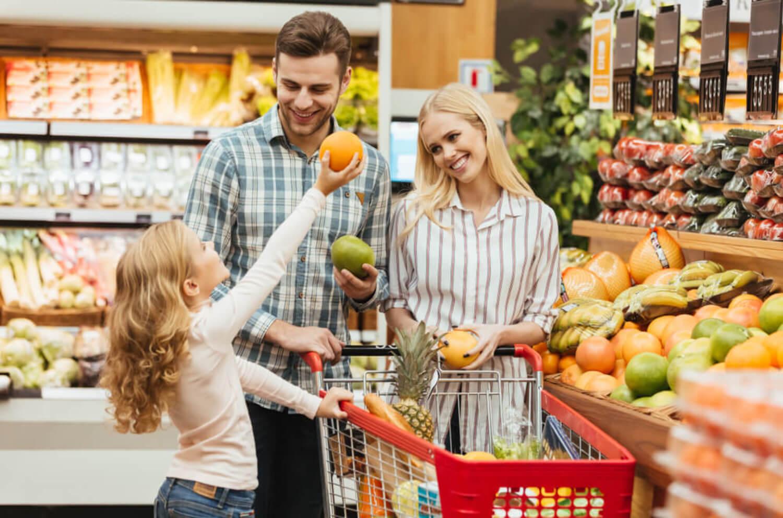 Padres comprando fruta en el supermercado con su hija para que aprenda matemáticas.