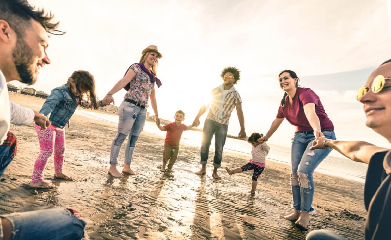 Padres e hijos dándose la mano en la playa por una educación intercultural.