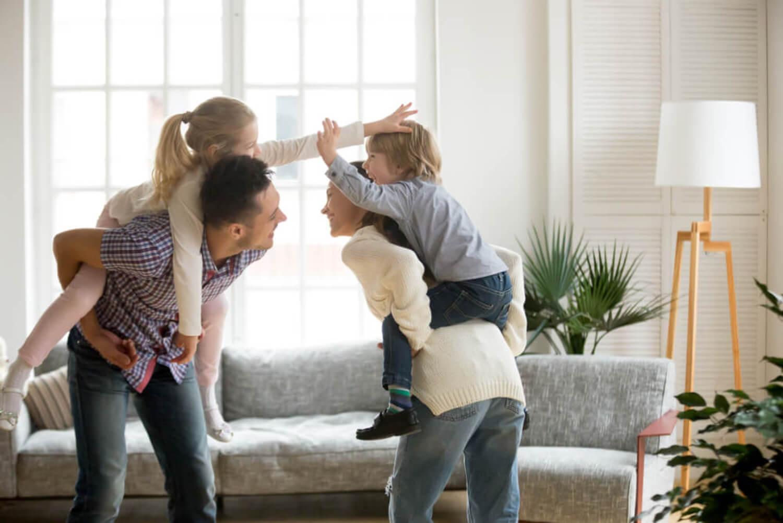 Padres jugando con sus hijos en el salón de casa.
