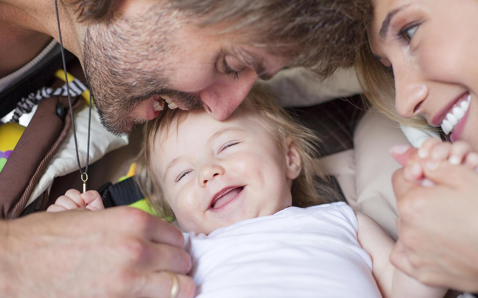 Padres jugando con su bebé y haciéndole reír para promover un apego seguro.
