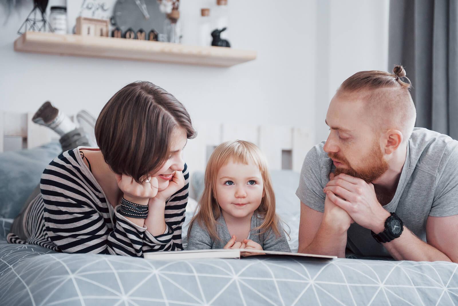 Padres leyendo un cuento a su hija antes de dormir, una de las recomendaciones para padres de bebés y niños de alta demanda.