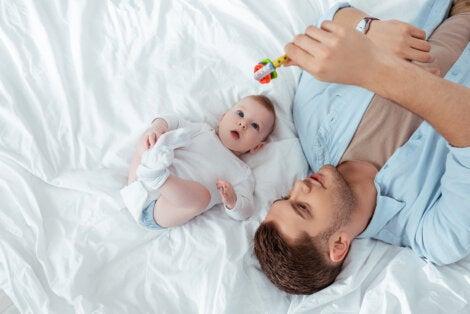 Padre jugando con su bebé con un sonajero.