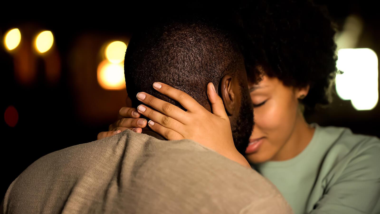 Pareja dándose un beso y un abrazo para intentar recuperar el deseo sexual tras el parto.