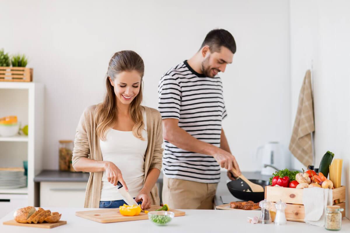 Pareja cocinando de manera saludable debido a la importancia de la vitamina E para la fertilidad.