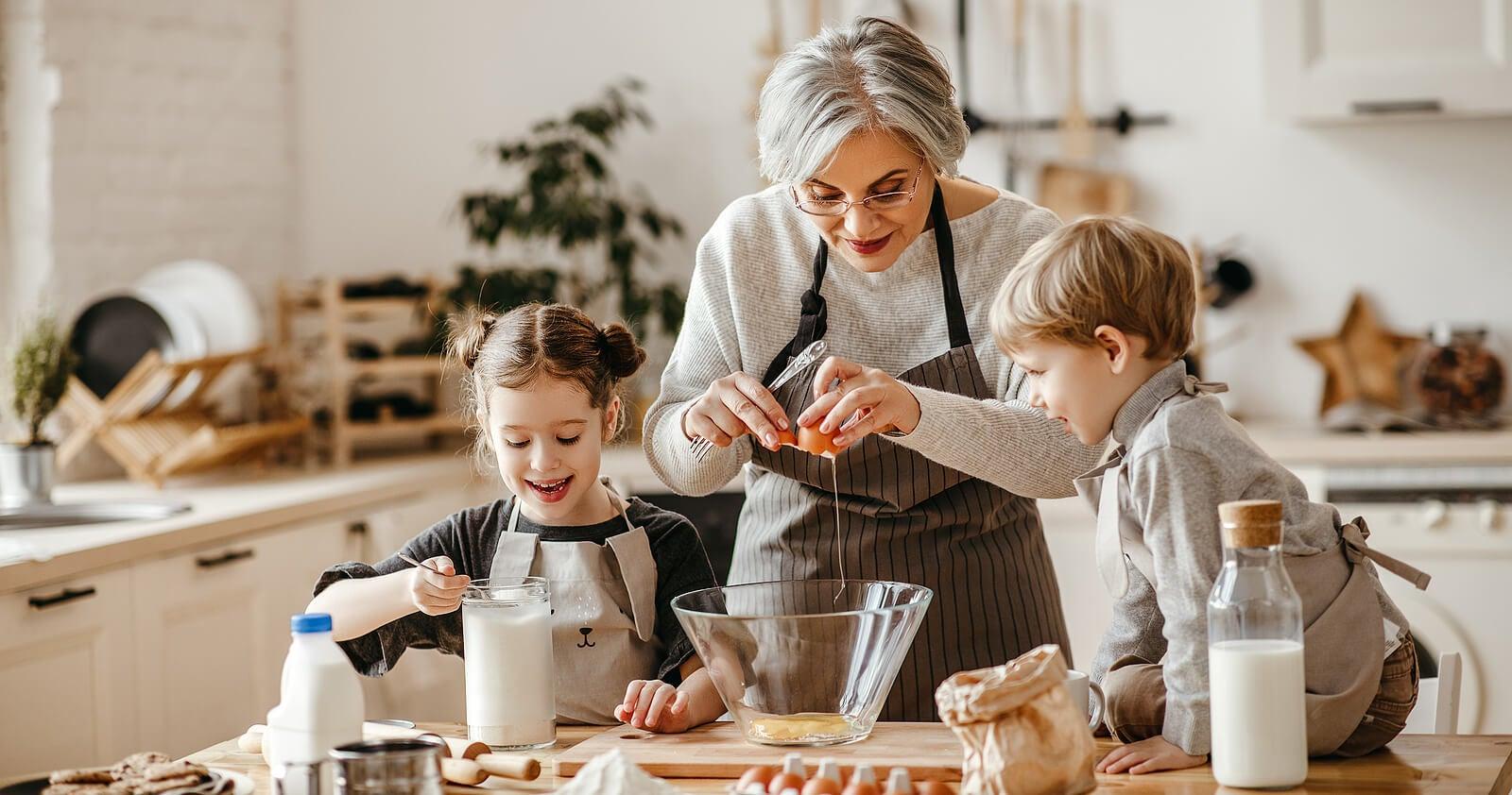 Abuela cocinando recetas de repostería con sus nietos.