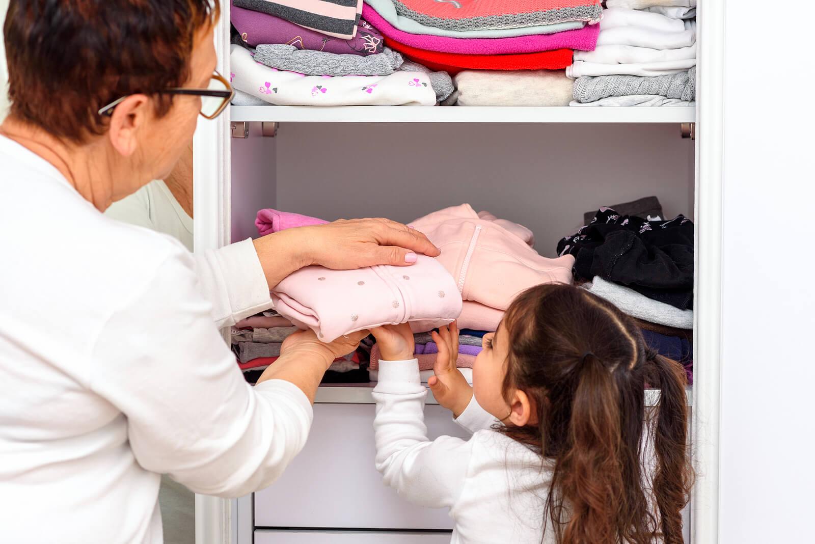 Niña ayudando a su abuela a guardar la ropa en el armario.