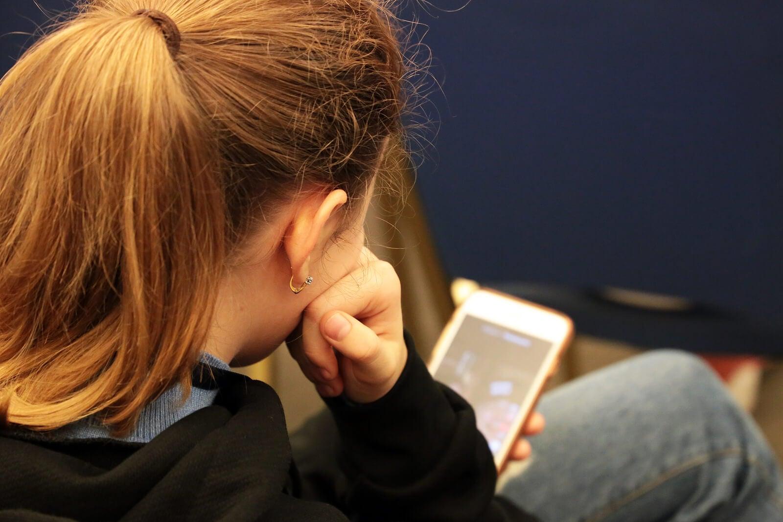 Adolescente adicta al móvil consultando sus redes sociales.