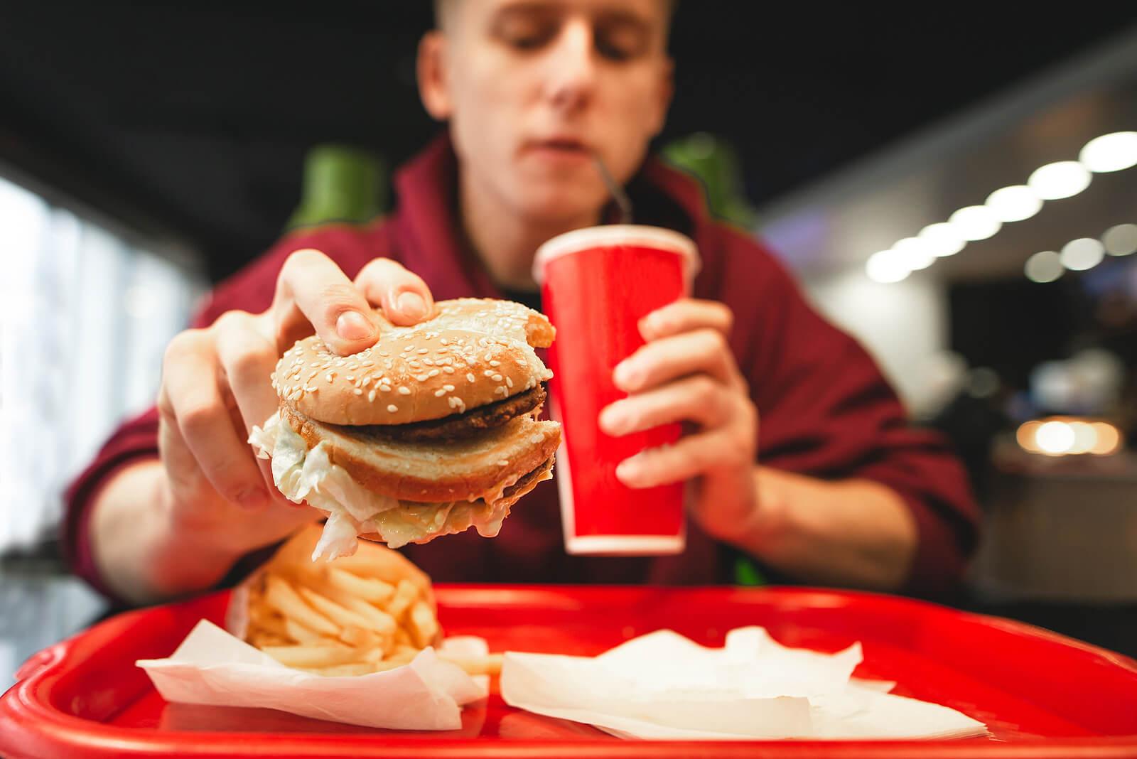 Adolescente comiendo una hamburguesa en una cadena de fast food.