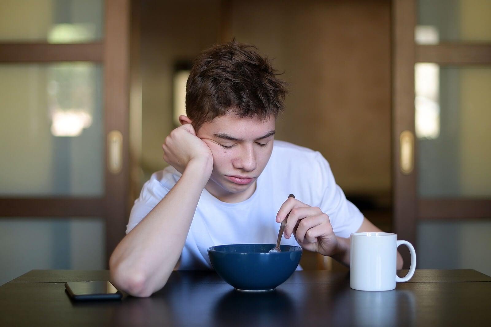 Adolescente desayunando con mucho sueño debido a que sufre el síndrome de fatiga crónica.