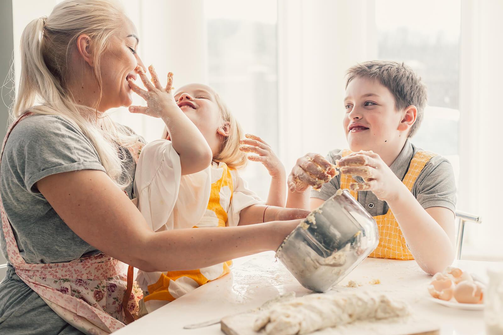 Madre con sus hijos haciendo actividades de cocina para niños.