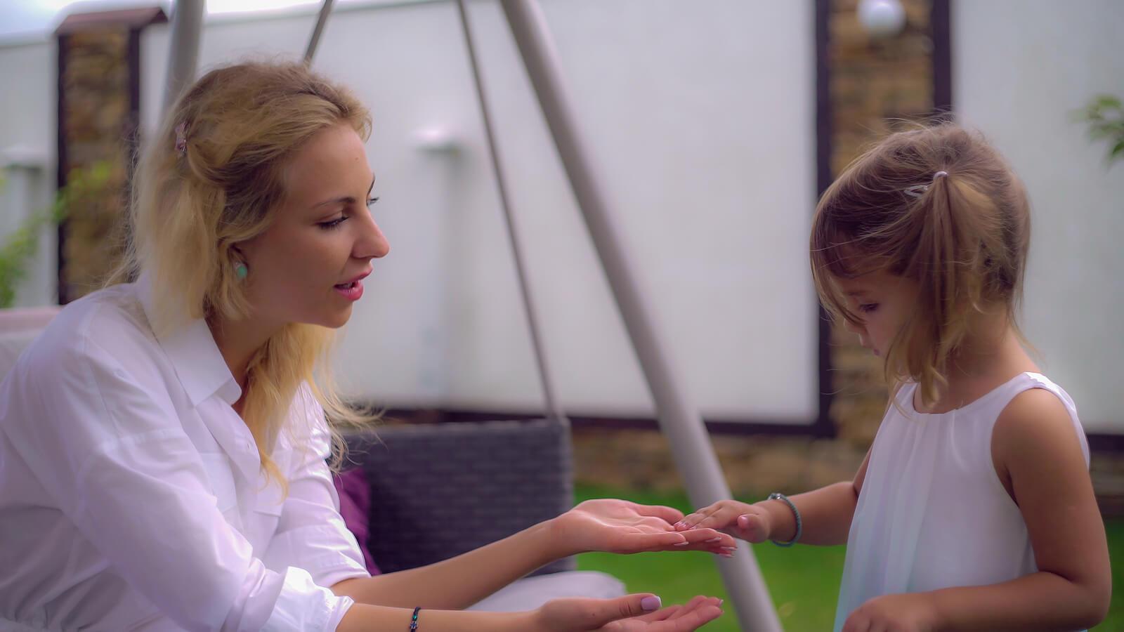 Madre hablando con su hija mientras juegan a las palmas.