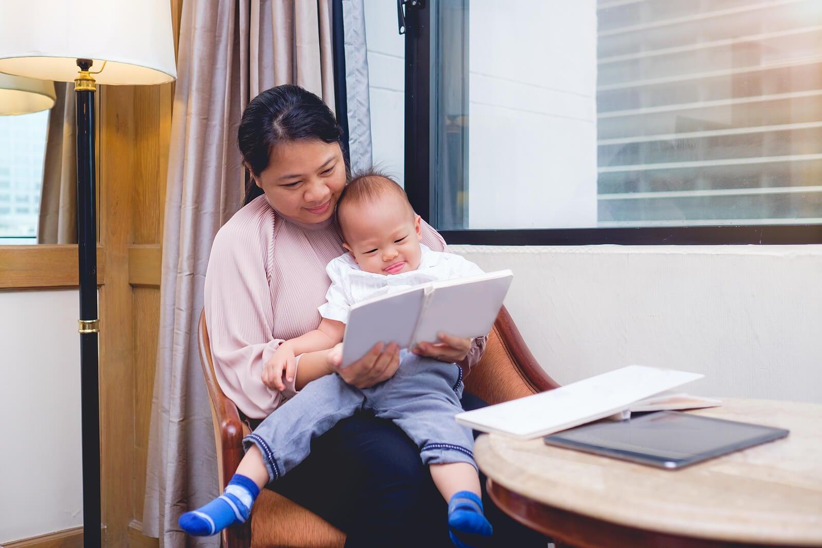 Mamá leyendo un libro de poesía infantil a su bebé.