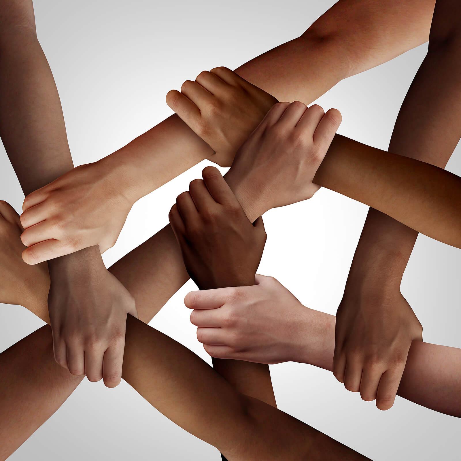 Manos y brazos de diferentes razas entrelazados para representar los derechos humanos.
