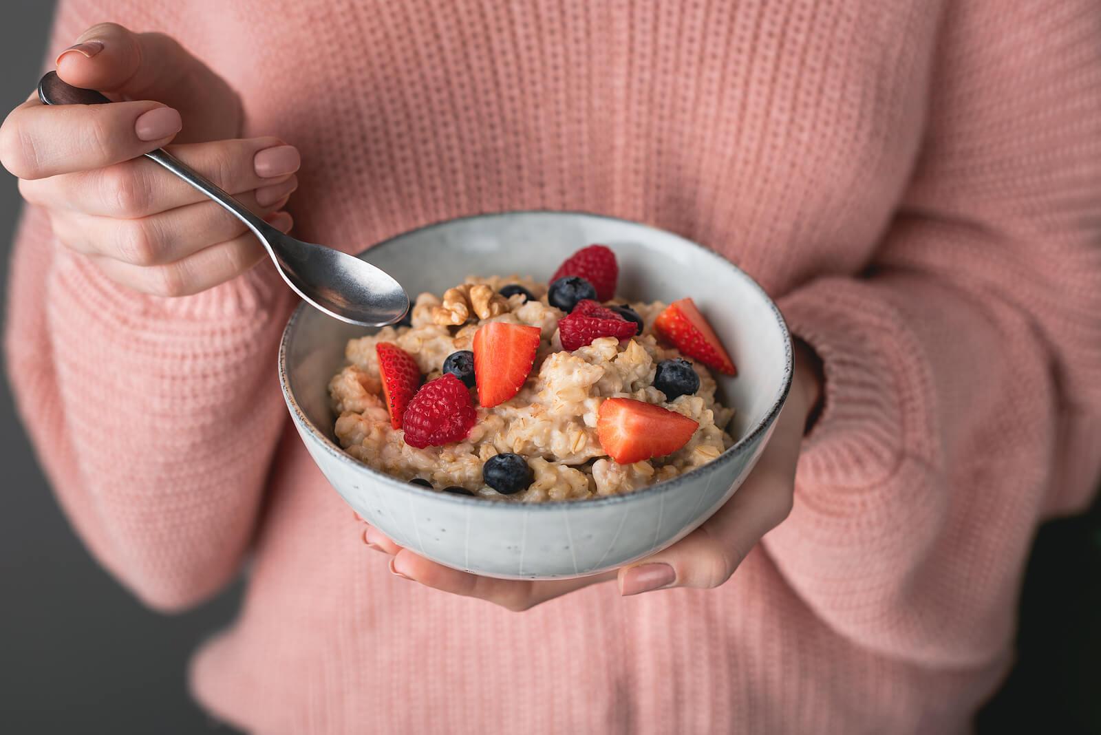 Mujer tomando un desayuno saludable para prevenir la diabetes gestacional.