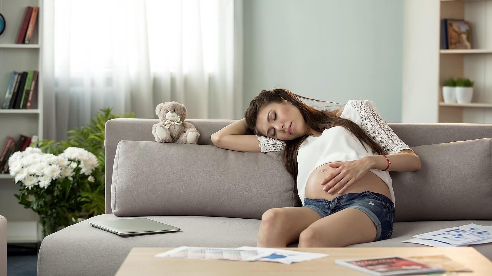 Mujer embarazada echándose una siesta en el sofá para mejorar el sueño durante el embarazo.