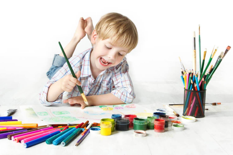 Niño haciendo el test del árbol con muchos colores.