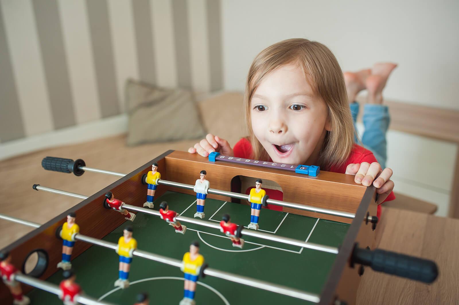 Niña impulsiva deseando jugar al futbolín.