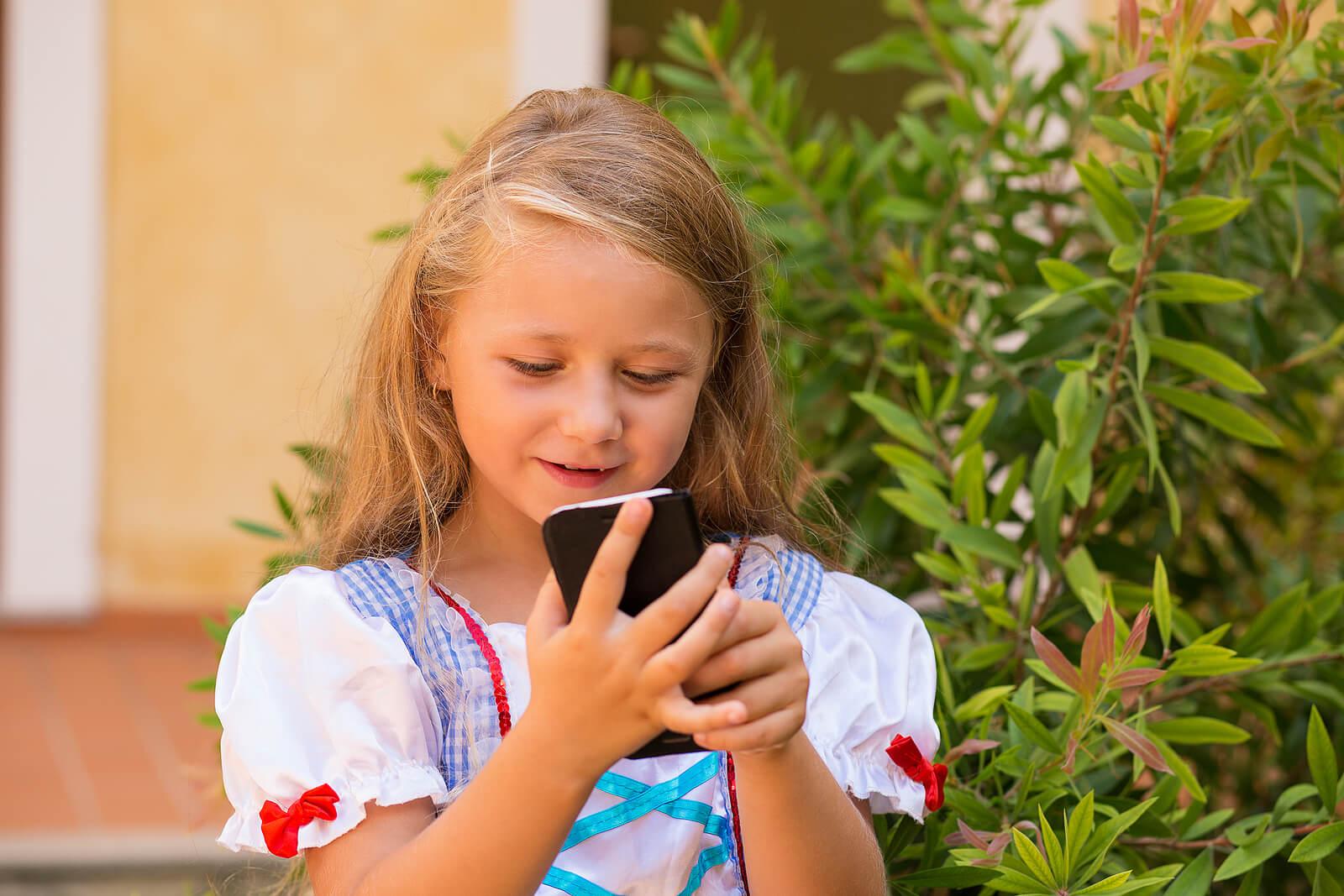 Niña enviando mensaje con el teléfono móvil.