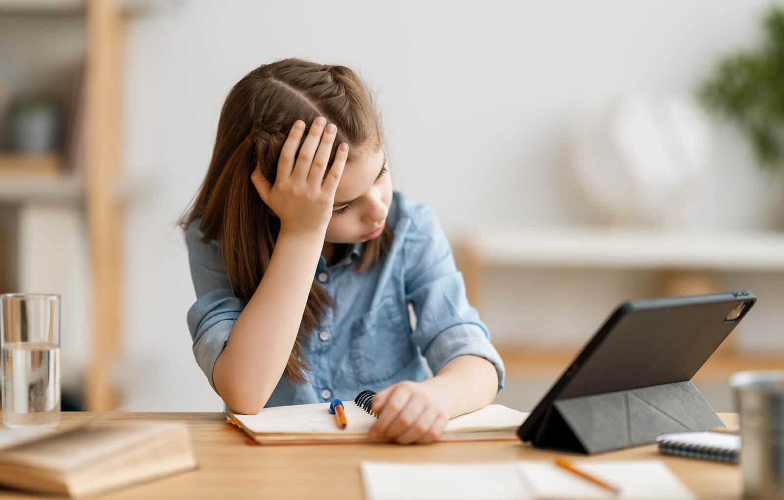 Niña haciendo los deberes frustada por su perfeccionismo en exceso.